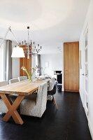Hellgraue Polstersessel und klassische Schalenstuhl an langem Esstisch aus Massivholz in modernem Wohnraum