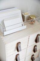 Transparente Kunststoffbox mit Karteikarten auf Schubladenkästchen verziert mit Ledergriffen