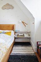 Kinderzimmer unter dem Dach mit Holzgestellbett, Regalablagen als Nachttisch und schwarz-weissem Teppichläufer