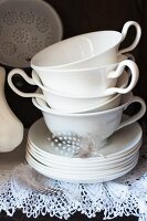 White china cups and saucers and speckled feather on lace shelf cover in antique cabinet