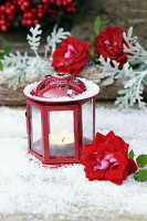 Tealight in red lantern and roses on artificial snow