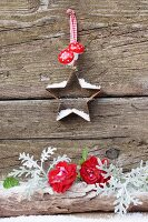 Star-shaped pastry cutter with artificial snow and toadstool decorations above roses and sea ragwort (Senecio bicolor)