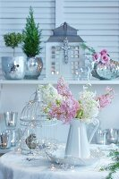 Christmas arrangement with pink and white hyacinths, ornamental bird cage and mercury silver vases