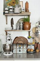 Mixer and vintage bread bin on stone worksurface below crockery on rustic wooden bracket shelves on white wall tiles