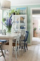 Various chairs around bouquet on wooden table and display case next to open door in rustic dining room
