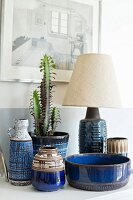 Blue, patterned ceramic containers and cactus in pot next to table lamp