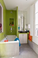 Bathtub next to partition with integrated washstand in bathroom with concrete floor and walls partially tiled in green