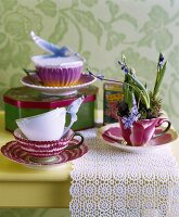 Vintage-style china cups and tin on lace doily on table