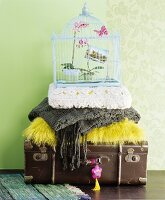 Stacked antique suitcase, cushions, blankets and vintage-style birdcage against pale green wall