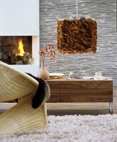 Wohnzimmer mit geschwungenem Korbstuhl auf Flokatiteppich, Sideboard mit Holzmaserung und Hängeleuchte mit Lampenschirm aus braunen Ferdern