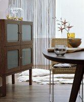 Wohnraum in Brauntönen mit Esstisch, Korbstuhl und halbhohem Holzschrank mit Milchglasscheiben