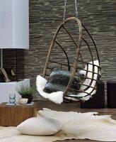Wohnzimmer mit gemütlichem Sitzplatz in Hängesessel mit Kuschelkissen und Schaffell