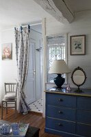 Table lamp and mirror on top of blue-painted chest of drawers next to curtain on doorway