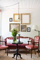 Symmetrically arranged gallery of pictures above antique upholstered furniture