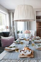 Table set with linen tablecloth and wooden plates below ceiling lamp with fabric lampshade