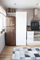 Kitchen in natural shades with bronze retro fridge and cowhide rug