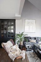 Ethnic accessories, black glass-fronted cabinet and sheepskin on leather armchair in living room