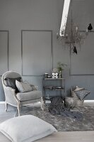 Stylish living room in shades of grey with antique armchair, fur rug and metal chandelier with bird ornaments