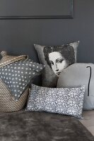 Various scatter cushions in shades of grey; plain, patterned and with picture of woman
