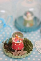 Vintage-style arrangement of snow globe on moss in pale green flan tin