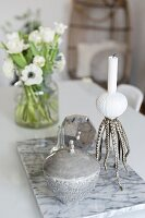 Tin and maritime candlestick on marble tile on table