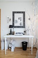 Fairy lights on white-painted branch next to white desk with black accessories
