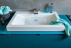A white sink built with a modern tap in to a petrol-coloured washstand