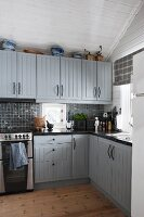 Rustic fitted kitchen with cabinets painted pale grey and white wood-clad walls