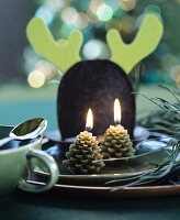 Place setting festively decorated with pine-cone-shapes candles
