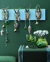 Christmas decorations in shades of green with baubles hanging from row of antlers