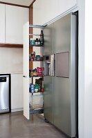 Open, sliding shelves next to stainless steel fridge-freezer in modern kitchen