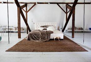Bedroom in open-plan attic interior with exposed beams