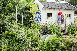 Two children outside play house in summery garden