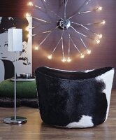 Cow-hide pouffe and designer standing ashtray in front of retro wall lamp