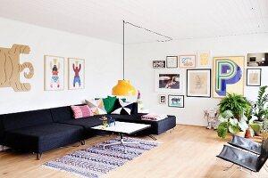 Anthrazitfarbene Sofalandschaft in geräumigem Wohnbereich mit Bildergalerie und skandinavischem Retroflair