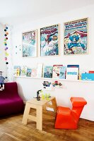 Children's books on wall-mounted shelves, framed comic posters and bold orange child's chair in Scandinavian interior