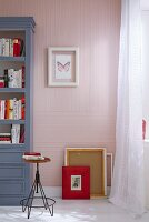 Picture frames on the floor against a wallpapered wall with a pin-stripped pattern in pink and white with a blue-grey shelf to the side