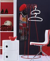 Retro cloakroom furniture in red and white with coat hangers and coat rack against dark wall