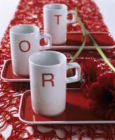 Three white china mugs printed with red letters and gerbera daisies on red trays on red, plastic table runner
