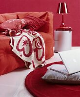 Loose-covered sofa with cosy blankets and scatter cushions in red and white interior; laptop on grey cushion on floor