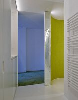 Curved, lime-green, mosaic-tiled wall in designer shower and blue-lit area beyond