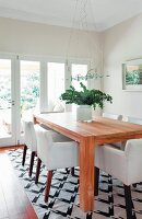 White armchairs around solid-wood table on black and white patterned rug in modern dining room