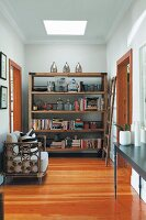 Armchair with rattan frame on wooden floor in front of rustic, modern shelving in hallway with skylight