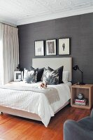 Dog lying on double bed with scatter cushions in modern bedroom with stucco ceiling and black wallpaper