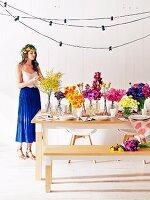 Junge Frau mit Blumenkranz an schlichtem Holztisch mit üppiger Blumendeko