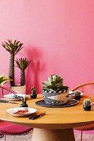 Runder gedeckter Holztisch vor pinkfarbener Wand mit Kakteen und Sukkulenten als Deko