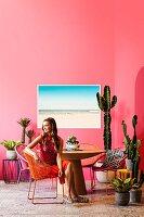 Retro-Urlaubsflair mit vielen Kakteen: Junge Frau sitzt auf Acapulco Chair am runden Tisch vor pinker Wand