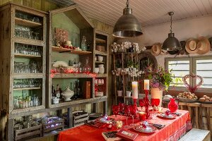 Christmas table set with red cloth and glasses in vintage interior in style of garden shed