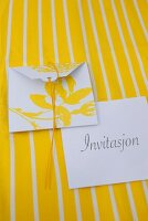 Invitation cards with yellow floral motif on white envelope on yellow and white striped surface
