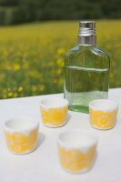 White beakers with yellow, retro pattern and flask of spirits on white surface outdoors